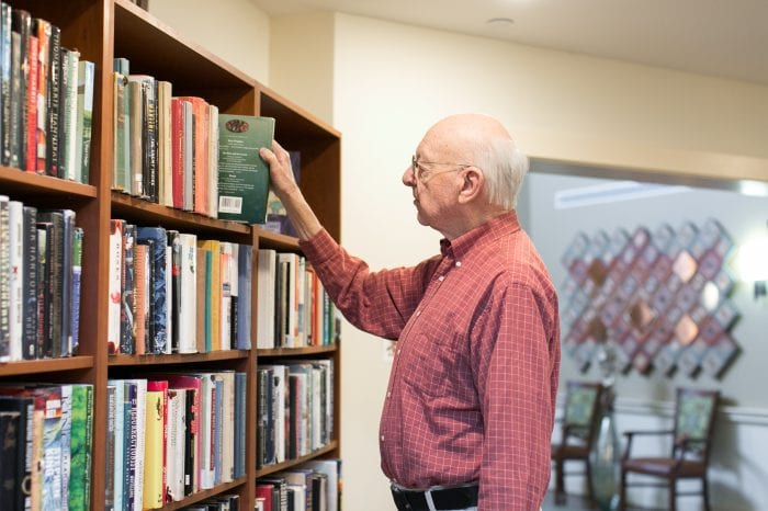 Elderly Man Walking and Reading