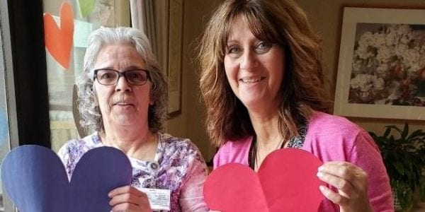 Two women holding paper heart cut outs