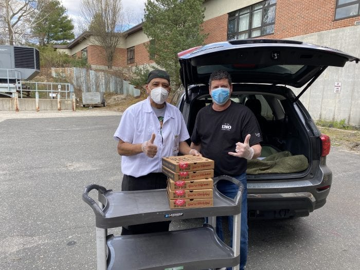Two men delivering pizza in a parking lot