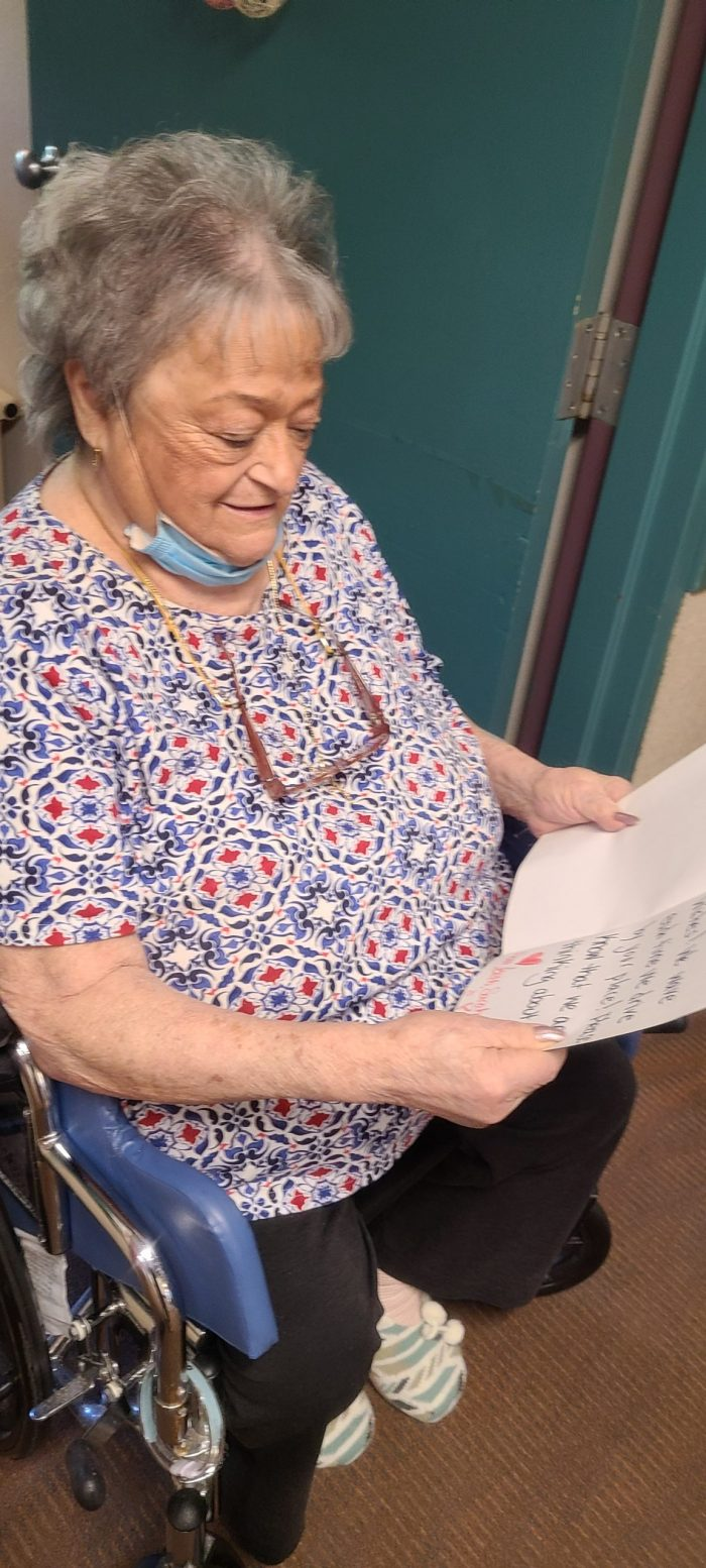 A JGS Lifecare resident reading her letter of love from the community