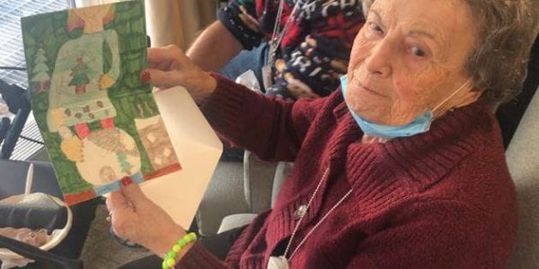 A resident of Ruth's House holding a holiday card and looking at the camera