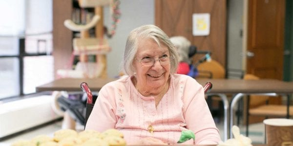 A resident happily decorating cupcakes