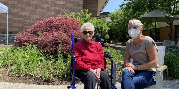 A resident and a home health aid relax outdoors.