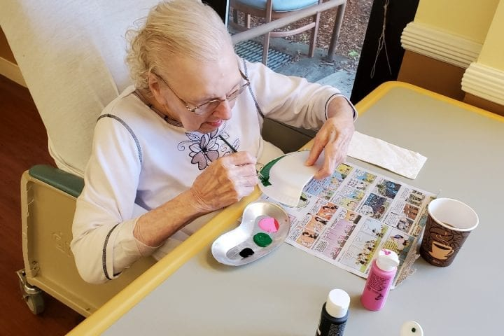 Lina Douville is in deep concentration as she paints