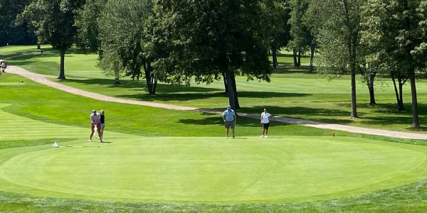Golfers on the green, putting, at the Frankel Kinsler Tournament
