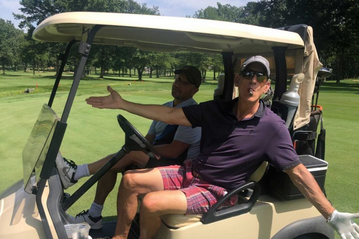 Two golfers driving a golf cart at the Frankel Kinsler Golf Tournament