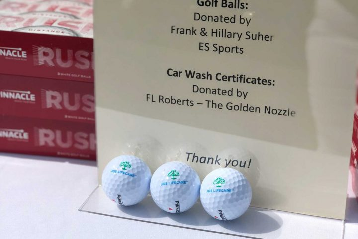 A sign with three golf balls that have JGS Lifecare logos printed on them.