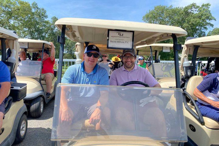 Adam Berman and a guest in a golf cart at the Frankel Kinsler Golf Tournament