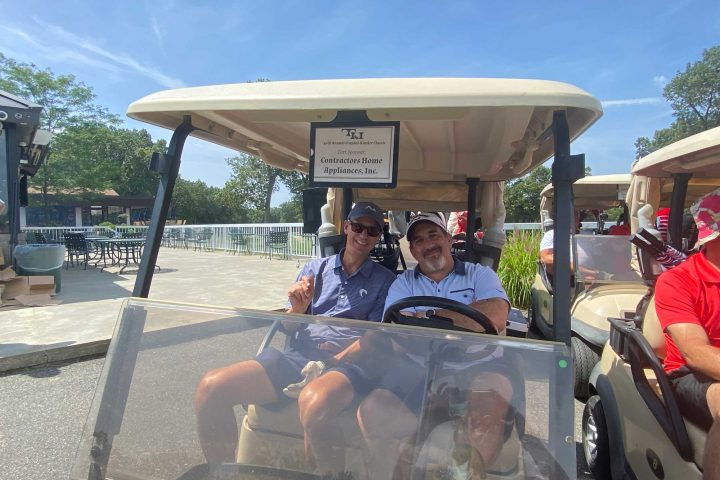 Two golfers in their golf cart at the Frankel Kinsler Golf Tournament