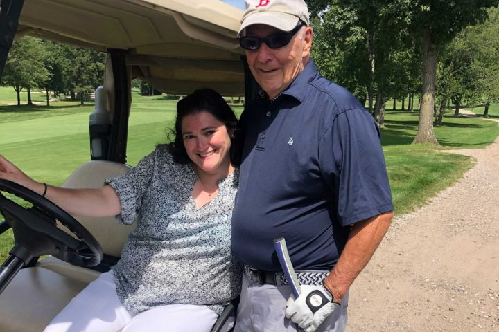 A couple posing in a golf cart at the Frankel Kinsler Golf Tournament