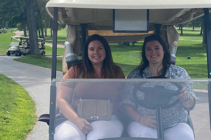 Two women driving in a golf cart