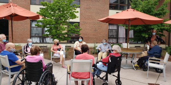 Residents of JNH enjoying a summer day on the patio outside Michael's Cafe.
