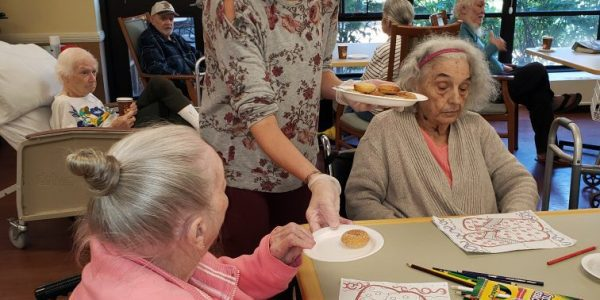 Holly, a staff member at JNH, hands out homemade donuts to residents.